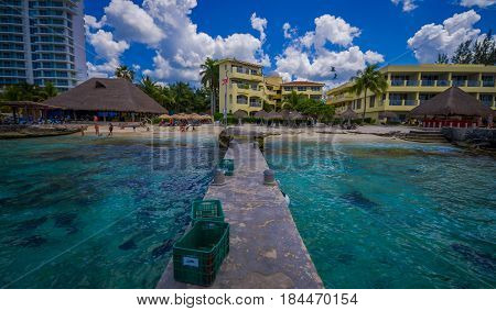 Beautiful vacation resort of Cozumel with some natural buildings and yachts, gorgeous blue ocean and sky.
