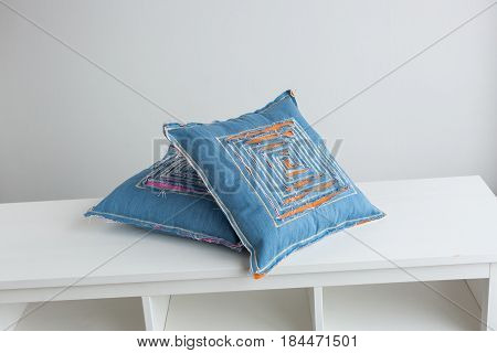 textile two blue pillows on a white background, close-up on the pillows decorated with stitching and designer decors in the form of a labyrinth cut in the fabric through which visible lining