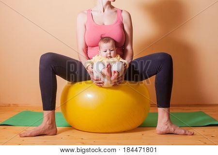 Caring mother doing sport exercises with her baby on fitball