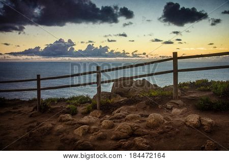 View od Cabo da Roca in Sintra - Roca Cape - cliffs and fence at sunset