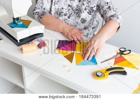 needlework and quilting in the workshop of a woman tailor - hands of tailor women put on the desktop the pieces of colored fabric, lay next to the scissors, buttons, pins, threads, rotary cutters