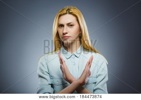 Serious woman making X sign with her arms to stop doing something.