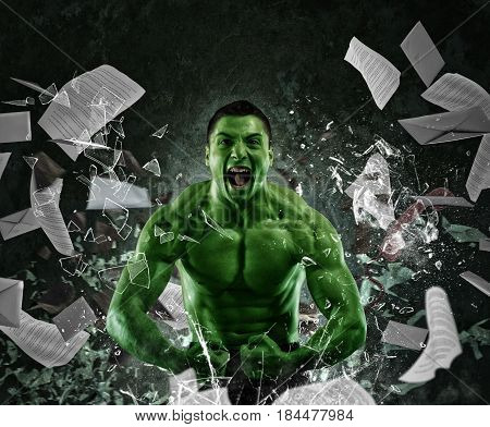 Green powerful muscular man screaming breaks a glass and throws sheets