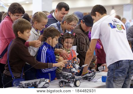 NOVOSIBIRSK, RUSSIA - OCTOBER 5, 2014: Children playing with robot demonstrated on 4th Russian Science Festival. The event aimed to popularization of science and demonstration of technical advances