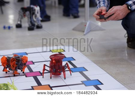 NOVOSIBIRSK, RUSSIA - OCTOBER 5, 2014: Man with remote control at a few robots demonstrated on the 4th Russian Science Festival. The event aimed to popularization of science and technical advances