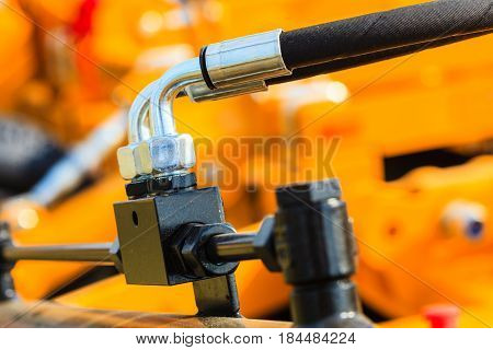 Industrial detailed pneumatic hydraulic machinery concept. Pump made of steel on orange machine closeup.