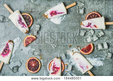 Healthy summer dessert. Blood orange, yogurt and granola popsicles on ice cubes over grey concrete background, top view, copy space, horizontal composition. Clean eating, dieting, weight loss concept