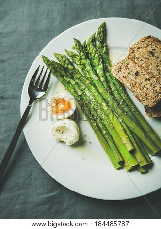 Cooked asparagus with soft-boiled egg, grilled bread and herbs on white round plate over grey textile background, top view. Clean eating food concept
