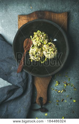 Homemade pistachio ice cream scoops with crashed pistachio nuts in dark plate over wooden board, grey concrete background, top view, vertical composition