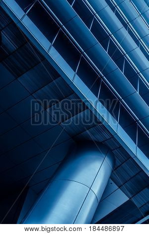 Metal column/pillar and part of the building in modern futuristic architecture. Public/office building exterior fragment