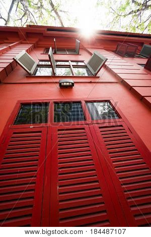 Vintage red building with wooden shutters from bottom to top view against sunny summer sky background