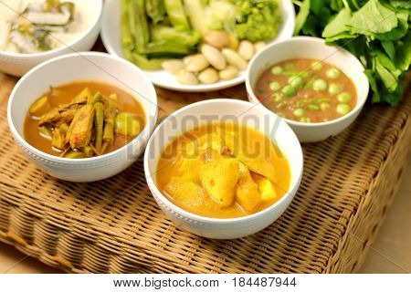 Sour soup with fish and bamboo shoot fish organs sour soup chili paste spicy thai food menu on rattan table
