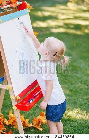 White Caucasian toddler child kid girl standing outside in summer autumn park drawing on easel with markers looking away playing studying learning back to school concept