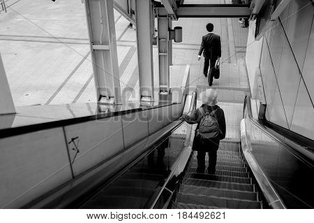 Old alone woman on escalator in city
