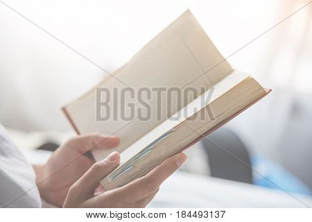 Close up woman hands holding a book on white background.