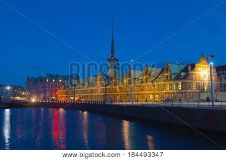 Old Stock Exchange at night in Copenhagen Denmark. Former stock exchange building along the canal with a distinctive spire.