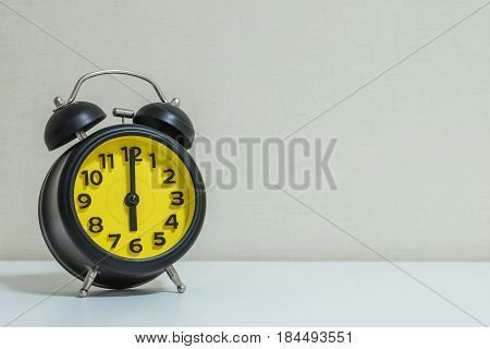 Closeup yellow and black alarm clock for decorate in 6 o'clock on white wood desk and cream wallpaper textured background with copy space
