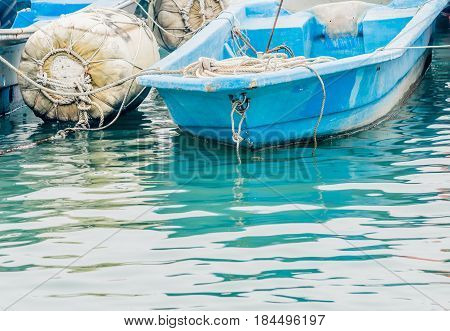 Closeup of small blue fishing boat floating in water tied to a large white buoy