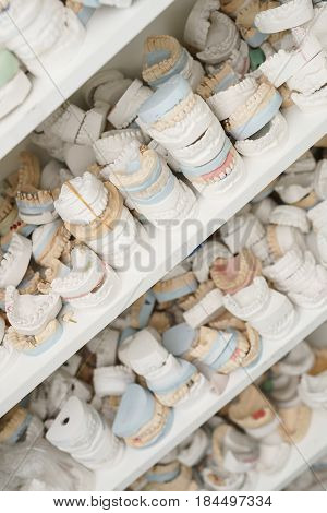 Piles of dentures lying on each other on several shelves close up shot in medical centre