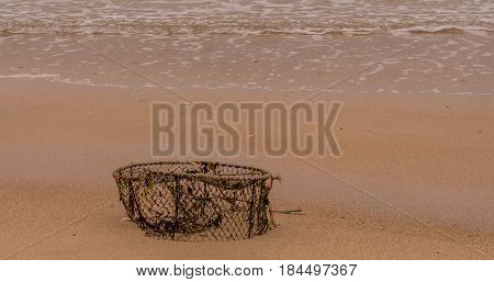 Large old crab cage abandoned on a beach with waves coming into shore in the background.