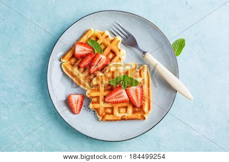Homemade belgian waffles with strawberrieson a blue background. Tasty breakfast with waffles.