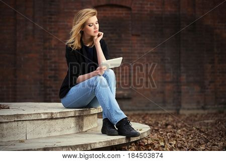 Young business woman using tablet computer in city street. Stylish fashion model in black jacket and blue jeans outdoor