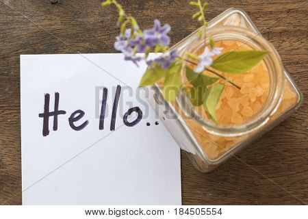 hello greeting message card and spa salt aroma of all flowers skin food with purple flowers on background wood