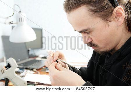 young man sculpting handmade miniature plastic toy house decoration craftsmanship hobby decor creation process