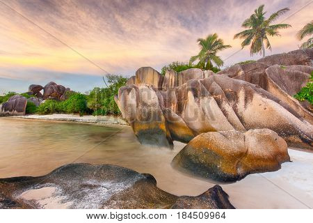 Beautifully shaped granite boulders and a dramatic sunset  at Anse Source d'Argent beach, La Digue island, Seychelles