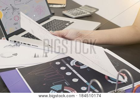 business hand holdding contract document on desk with office supplies. concept negotiation legal agreement.
