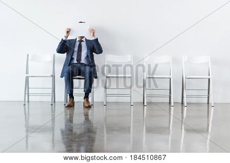 Businessman Covering Face With Paper