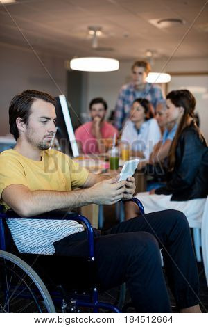 Concentrated physically disabled man on wheelchair using tablet in office