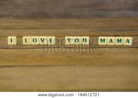 Close-up of I love you mom block on wooden background