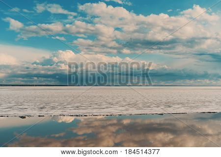 Scenery view of frozen sea during ice drift on springtime with dramatic teal sky and clouds having reflections in melt water on evening in Novosibirsk Russia