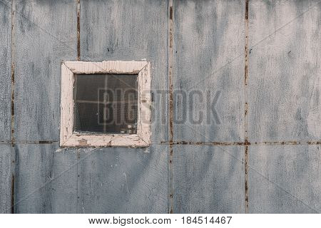 Small shabby single window with corrugated glass on facade of handmade bathhouse textured wall of painted ruberoid with multiple small cracks and metal stripes on it with copy space for text message
