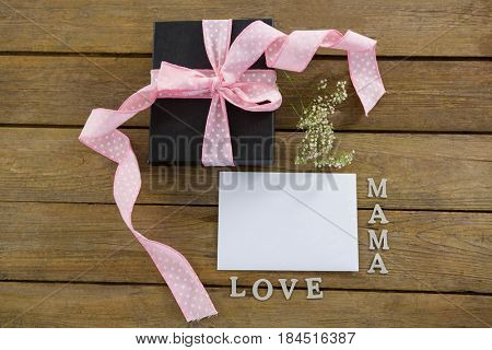 Close- up of gift box with mama love text on wooden plank