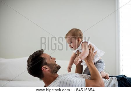 Father playing with his baby in bedroom at home