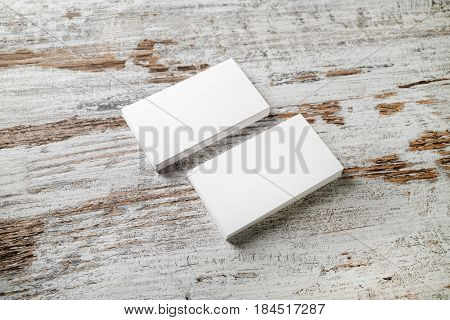 Mockup of blank business cards stack on wooden table background. For design presentations and portfolios. Selective focus.