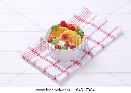 bowl of american pancakes with white yogurt and fresh raspberries on checkered dishtowel