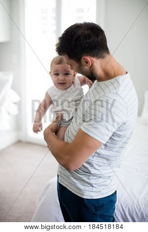 Father holding his crying baby girl at home