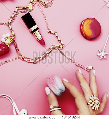 woman hands holding macaroons with lot of girl stuff on pink background, girls accessories concept close up