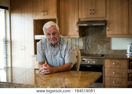Portrait of senior man sitting with hands clasped in the kitchen at home
