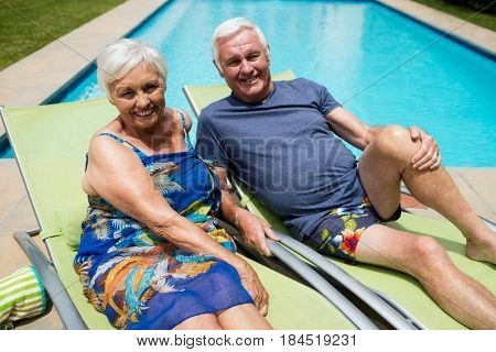 Portrait of senior couple relaxing on lounge chair at poolside