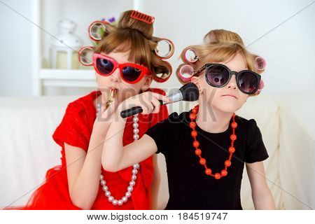 Two funny little girls with curlers in their hair make themselves a make-up. Kid's fashion. Family at home.