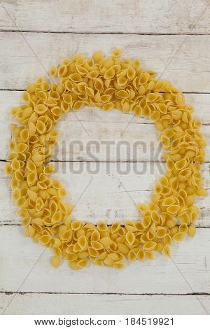 Fettuccine pasta forming a circle on wooden table