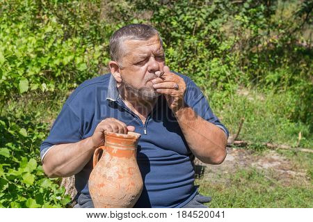Ukrainian senior peasant taking an old clay jug and smoking cigarette rolled by himself with an old newspaper scrap and tobacco cultivated on an own garden