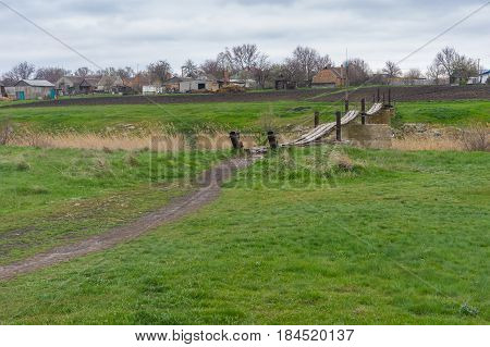 Spring landscape with meadow and old foot-bridge over small river Tomakivka in Topyla village central Ukraine