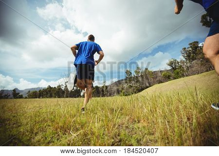 Rear view of fit man running in bootcamp