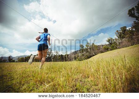 Rear view of fit woman running in bootcamp