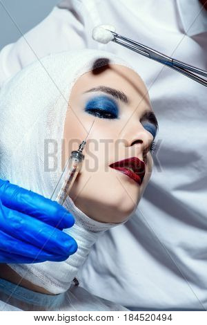 Beauty, fashion and medicine, plastic surgery. Portrait of an attractive young woman in bandages and hospital gown. Studio shot.